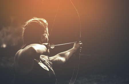 Atletenmeisje, die op het doel richten en een pijl schieten. Boogschieten. Stockfoto