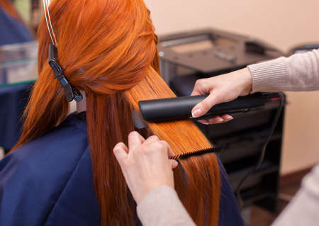 Hairdresser makes hairstyle girl with long red hair in a beauty salon. Straightening hair ironing. Professional hair care. Archivio Fotografico