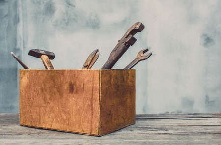 In the old wooden box there are workers, rusty tools - a hammer, a wrench, a gas wrench, chisel and garden sheath.