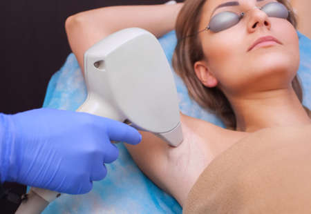 The cosmetologist does the laser hair removal procedure in the armpit zone, to a young woman in a beauty salon.