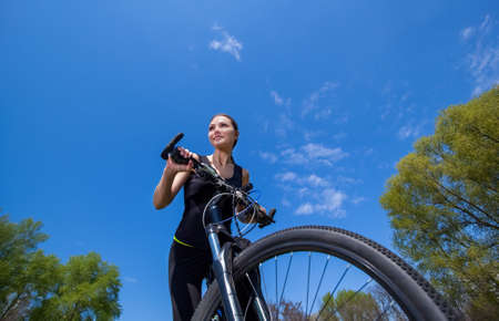 Girl athlete in black tracksuit rides a bike in the morning in the park. Healthy lifestyle.