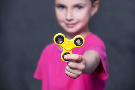 Little beautiful girl in pink t-shirt is playing yellow spinner in hand on the street. Archivio Fotografico