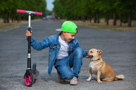 depreciation: A small boy with a scooter sits next to a dog and strokes her in the park for a walk.