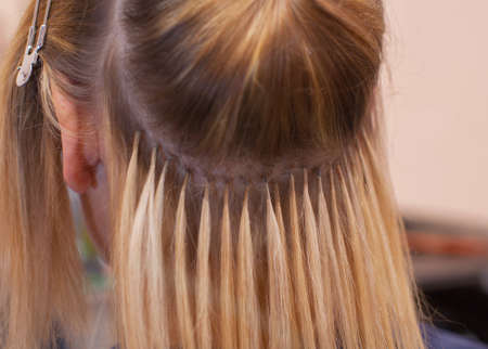 The hairdresser does hair extensions to a young girl, a blonde in a beauty salon. Professional hair care.