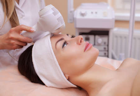 lymphatic drainage therapy: The doctor-cosmetologist makes the procedure Cryotherapy of the facial skin of a beautiful, young woman in a beauty salon.Cosmetology and professional skin care. Stock Photo