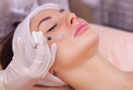 inyeccion intramuscular: El médico cosmetólogo realiza el procedimiento de inyección de Botulinotoxin para apretar y suavizar las arrugas en la piel de la cara de una hermosa mujer joven en un salón de belleza.Cosmetología cuidado de la piel.