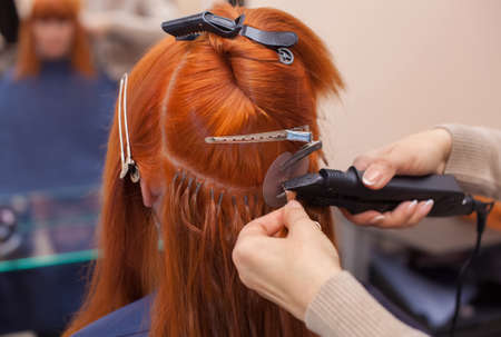 The hairdresser does hair extensions to a young, red-haired girl, in a beauty salon. Professional hair care. Stock Photo