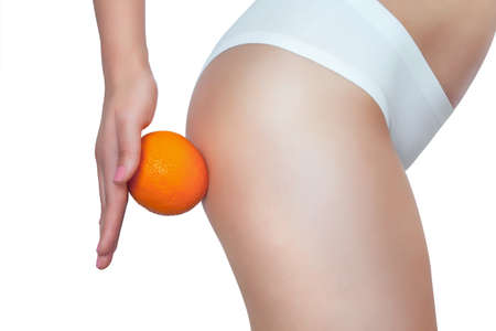 A thin girl is holding an orange by her ass. Concept of sport and healthy lifestyle.