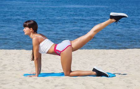 A beautiful sports woman is engaged in gymnastics against the background of the sea coast. Imagens