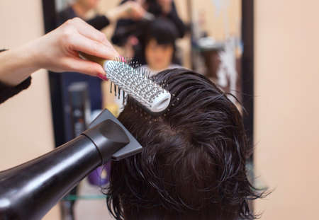 The hairdresser dries her hair a brunette girl in a beauty salon. Stock Photo