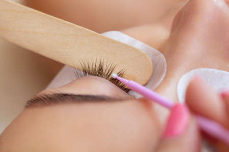Eyelash removal procedure close up. Beautiful Woman with long lashes in a beauty salon. Eyelash extension. Stock Photo