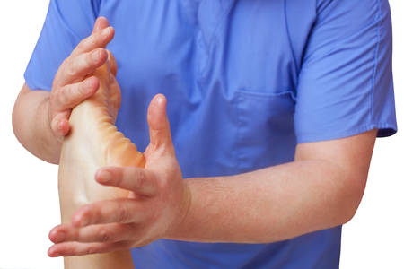 The doctor-podiatrist does an examination and massage of the patients foot in the clinic. Stock Photo