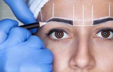 Maquillaje permanente para cejas de mujer hermosa con cejas gruesas en salón de belleza. Esteticista de cerca haciendo tatuaje ceja. Foto de archivo