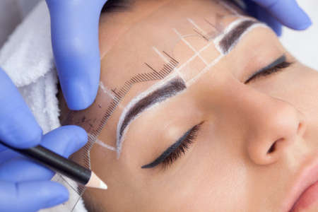 Permanent make-up for eyebrows of beautiful woman with thick brows in beauty salon. Closeup beautician doing  tattooing eyebrow. Stock Photo