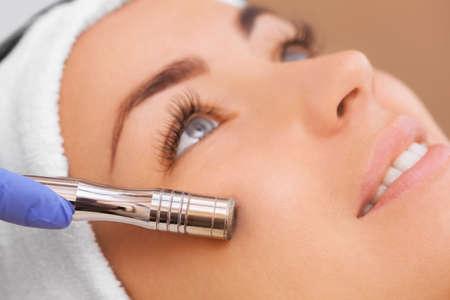 Die Arzt-Kosmetikerin macht die Prozedur Microdermabrasion der Gesichtshaut einer schönen, jungen Frau in einem Beauty-Salon.Kosmetologie und professionelle Hautpflege. Standard-Bild - 87181728