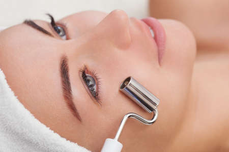 The cosmetologist makes the apparatus a procedure of Microcurrent therapy of a beautiful, young woman in a beauty salon. Cosmetology and professional skin care. Stock Photo
