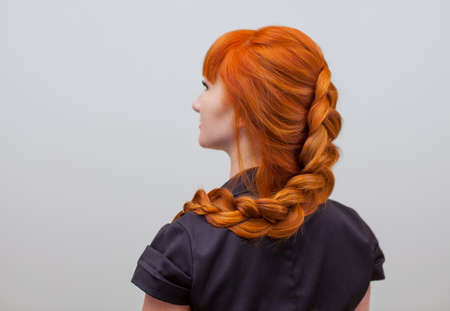 뷰티 살롱에서 프랑스 머리 띠와 함께 꼰 긴 빨간 머리를 가진 아름 다운 소녀. 전문 헤어 케어 및 헤어 스타일 만들기. 스톡 콘텐츠 - 87589138