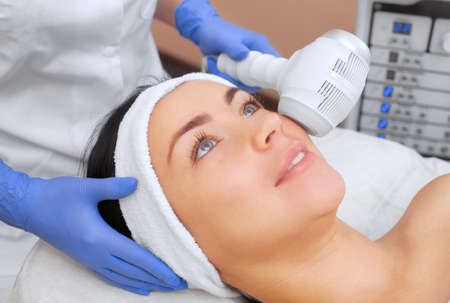 The cosmetologist makes the procedure Cryotherapy of the facial skin of a beautiful, young woman in a beauty salon.Cosmetology and professional skin care.
