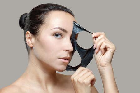 een zwart masker op het gezicht van een mooie vrouw. Spabehandelingen en verzorging van de katten in de schoonheidssalon.