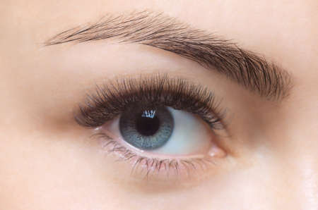 Eyelash removal procedure close up. Beautiful Woman with long lashes in a beauty salon. Look at the camera.