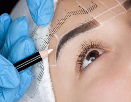Permanent make-up for eyebrows of beautiful woman with thick brows in beauty salon. Closeup beautician doing  tattooing eyebrow. 스톡 콘텐츠