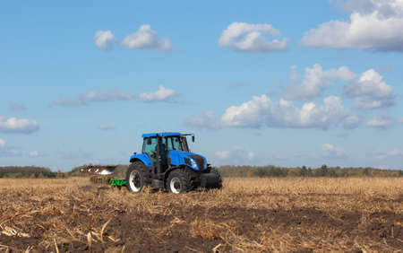 a large blue tractor, plowing field against the beautiful sky. Work of agricultural machinery. Harvest