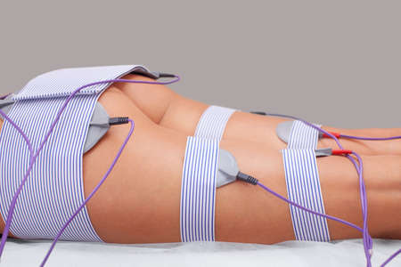 The procedure of myostimulation on the legs and buttocks of a woman in a beauty salon. Caring for the body, reducing excess weight.