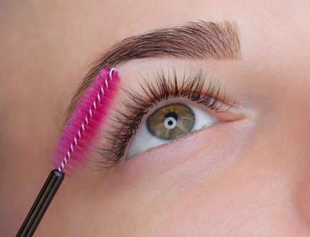 Beautiful Woman with long eyelashes in a beauty salon. Eyelash extension procedure. Lashes close up Stock fotó