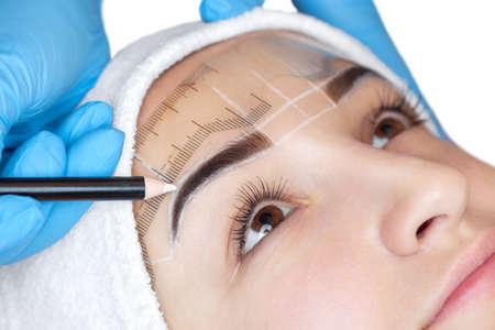 Maquiagem permanente para sobrancelhas de mulher linda com sobrancelhas grossas no salão de beleza. Closeup beautician fazendo sobrancelha tatuada. Foto de archivo