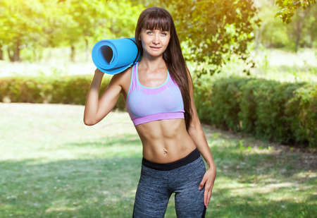 Beautiful sports woman is engaged in gymnastics in the park.
