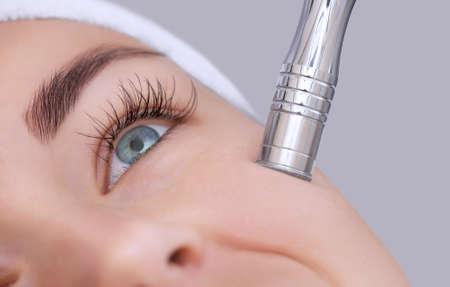 La cosmetóloga realiza el procedimiento de Microdermoabrasión de la piel facial de una bella y joven mujer en un salón de belleza. Cosmetología y cuidado profesional de la piel. Foto de archivo