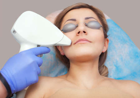 The cosmetologist does the laser hair removal procedure on the face Stock Photo