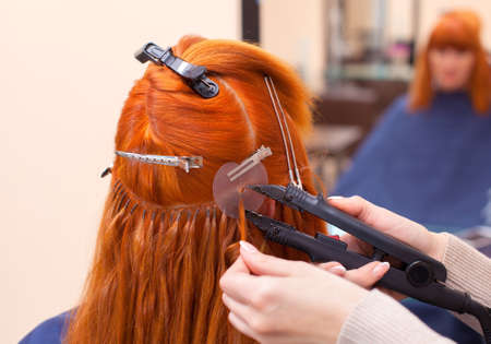 The hairdresser does hair extensions to a young, red-haired girl, in a beauty salon. Professional hair care. Stockfoto