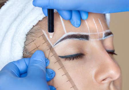 Permanente make-up voor wenkbrauwen van mooie vrouw met dikke browsjes in schoonheidssalon. Close-up schoonheidsspecialist die tatoeëren wenkbrauw doet. Stockfoto - 91814090