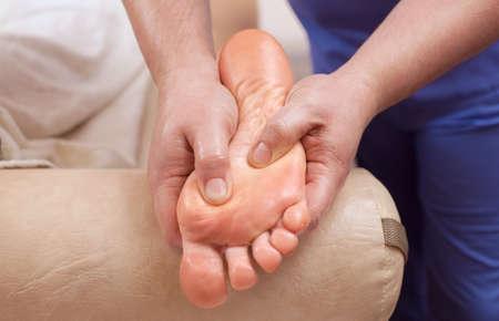 De arts-podoloog doet een onderzoek en massage van de voet van de patiënt in de kliniek. Stockfoto - 91211634