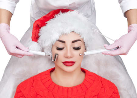 The cosmetologist makes the  procedure of Microcurrent therapy of a beautiful, young woman in Santa Claus hat in a beauty salon. New Years and Cosmetology concept.