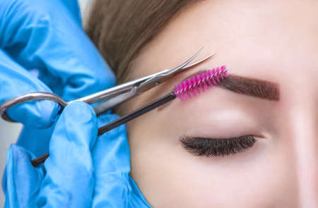The make-up artist cuts her eyebrows with scissors. A girl with beautiful long eyelashes and well-groomed eyebrows.