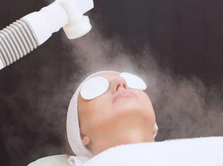 Das Verfahren der Dämpfen der Haut eines Gesichts einer jungen Frau vor der Reinigung eines Haut im Salon Standard-Bild