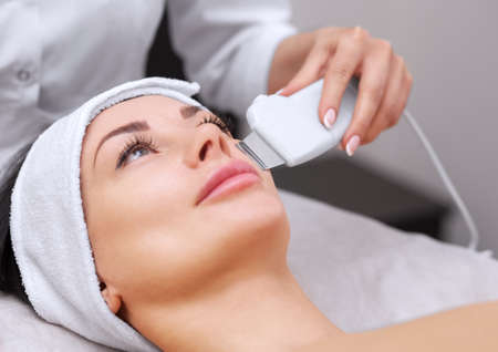 The doctor-cosmetologist makes the apparatus a procedure of ultrasound cleaning of the facial skin of a beautiful, young woman in a beauty salon. Cosmetology and professional skin care.