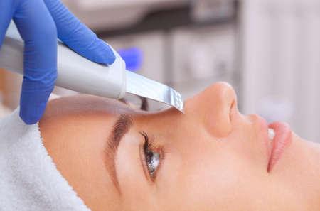 De arts-schoonheidsspecialist maakt het apparaat een procedure voor ultrasone reiniging van de gezichtshuid van een mooie, jonge vrouw in een schoonheidssalon. Cosmetologie en professionele huidverzorging. Stockfoto