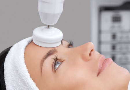 The cosmetologist makes the apparatus a procedure of Hardware face cleaning with a soft rotating brush of a beautiful, young woman in a beauty salon. Cosmetology and professional skin care.