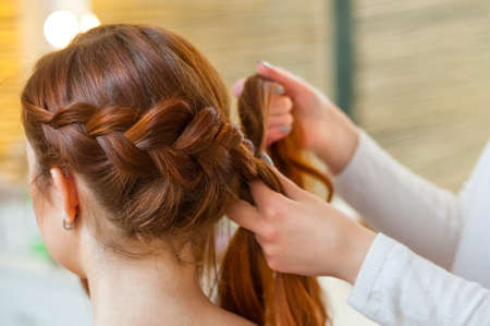 Beautiful girl with red hair, hairdresser weaves a  braid close-up, in a beauty salon. Professional hair care and creating hairstyles.
