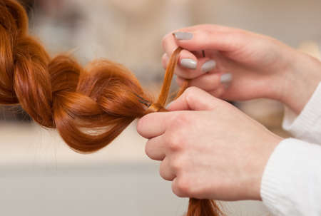 Beautiful girl with long, red-hair, hairdresser weaves a  braid close-up, in a beauty salon. Professional hair care and creating hairstyles.