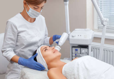 The doctor-cosmetologist makes the apparatus a procedure of Hardware face cleaning with a soft rotating brush of a beautiful, young woman in a beauty salon. Cosmetology and professional skin care.