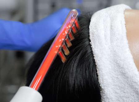 의사 - 미용사는 미용 살롱에서 아름답고 젊은 여성의 머리카락에 미세 전류 요법을 만듭니다. 화장품 및 전문 피부 관리.