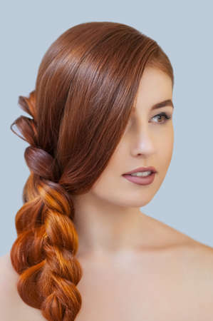 Beautiful girl with long red hair, braided with a French braid, in a beauty salon. Professional hair care and creating hairstyles. Stock Photo