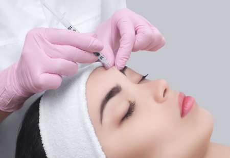 The doctor cosmetologist makes the Rejuvenating facial injections procedure for tightening and smoothing wrinkles on the face skin of a beautiful, young woman in a beauty salon.Cosmetology skin care.