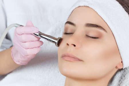 La cosmetóloga realiza el procedimiento de Microdermoabrasión de la piel facial de una bella y joven mujer en un salón de belleza. Cosmetología y cuidado profesional de la piel.