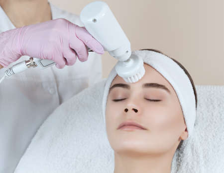 The cosmetologist makes the apparatus  procedure of Hardware face cleaning with a soft rotating brush of a beautiful, young woman in a beauty salon. Cosmetology and professional skin care.