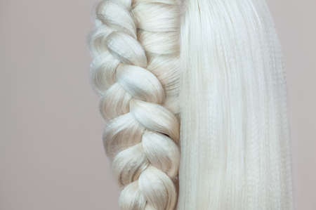 Beautiful girl with blonde hair, hairdresser weaves a  braid close-up, in a beauty salon. Professional hair care and creating hairstyles. 스톡 콘텐츠